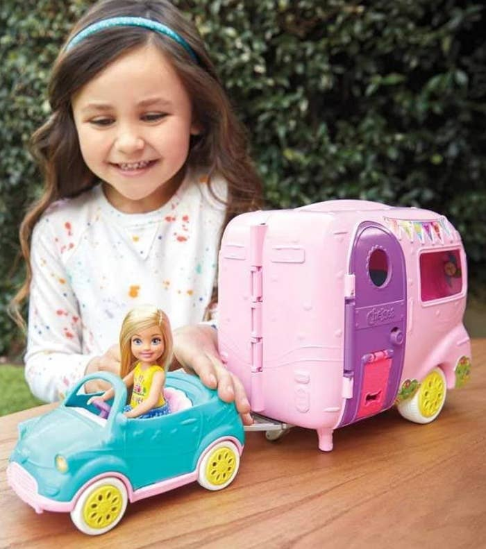 child playing with barbie doll camper set