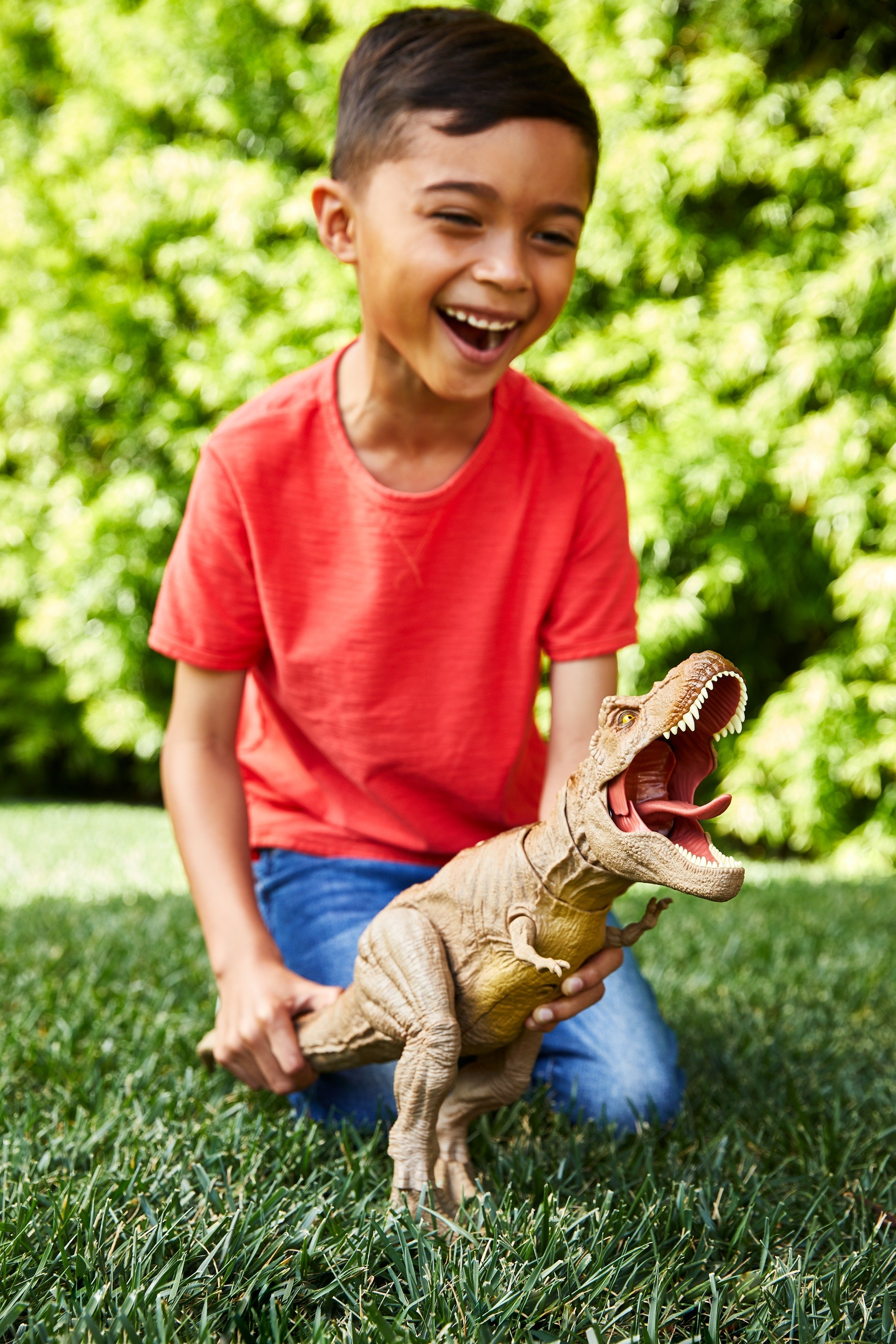 kid playing with a t rex figure from jurassic world while in the grass