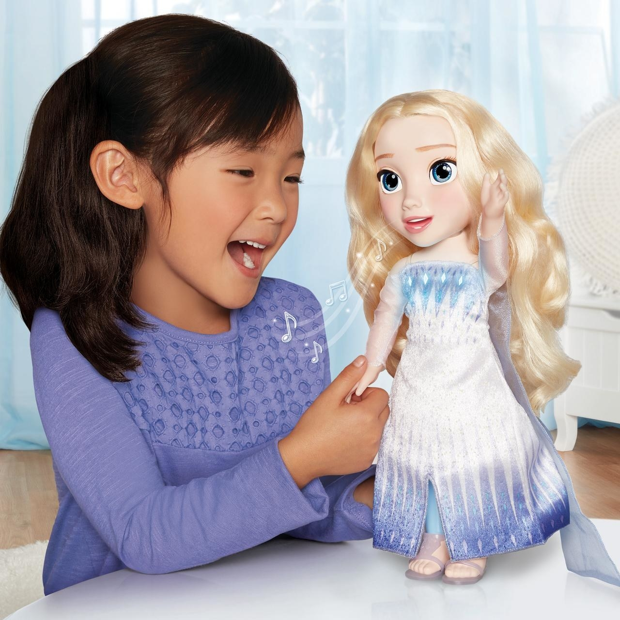 child playing with an elsa doll that sings and moves along