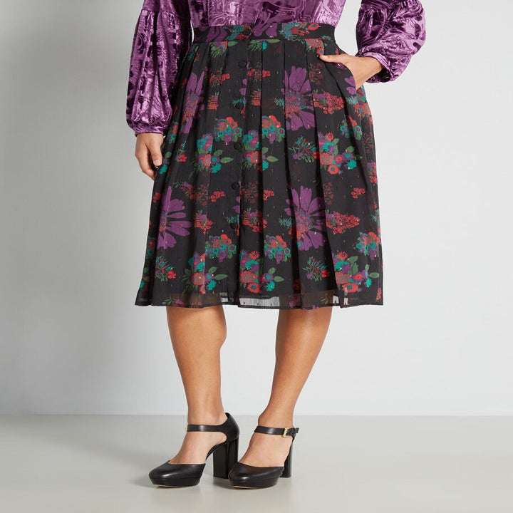 black pleated skirt with purple, green, and red floral pattern