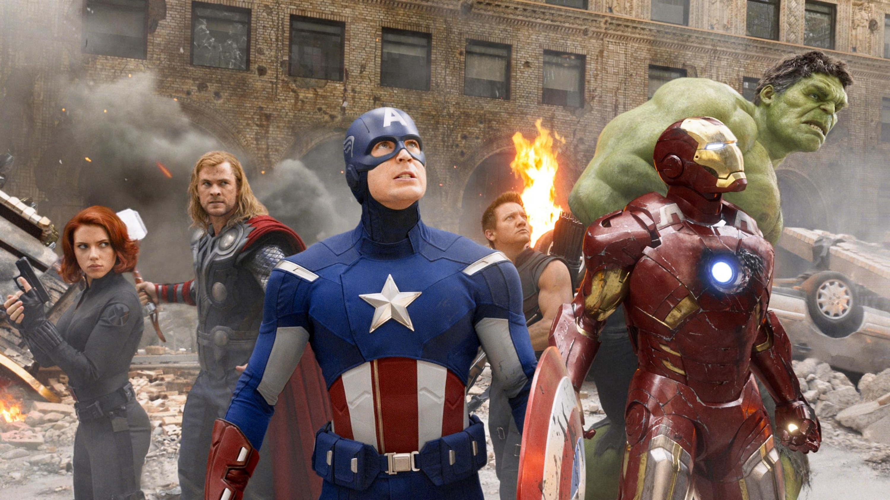 Black Widow, Thor, Captain America, Hawkeye, Iron Man and the Hulk looking at an enemy in the distance