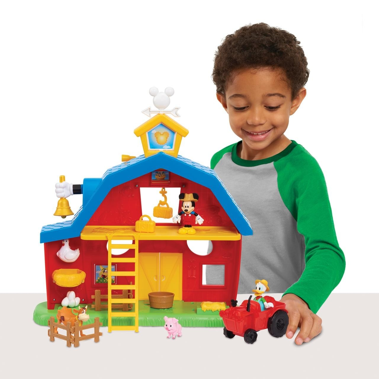 kid pushing donald duck in a toy tractor in front of a disney junior mickey barnyard playset
