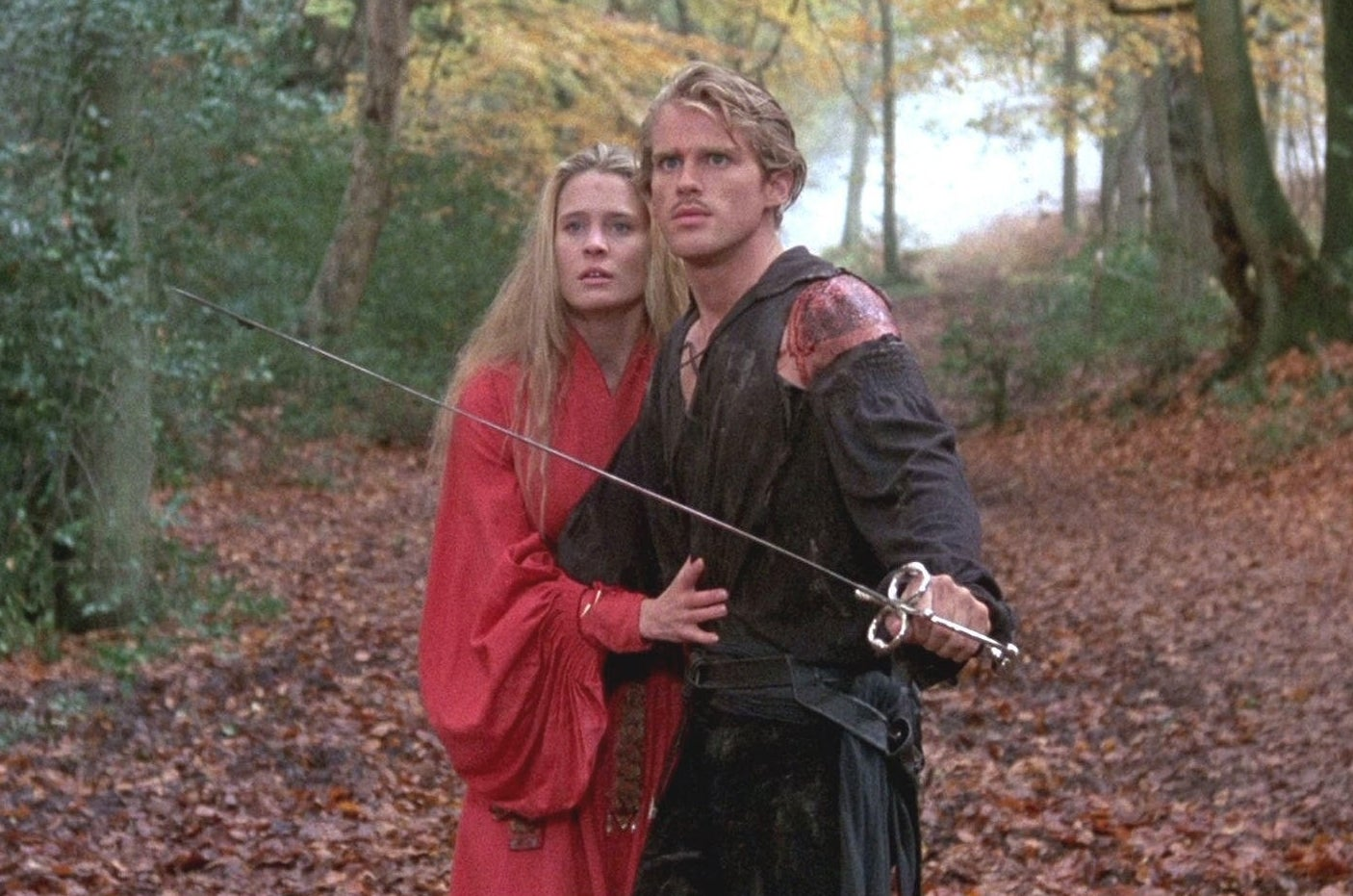 Westley and Buttercup in the forest; Westley has his sword drawn, while protecting Buttercup