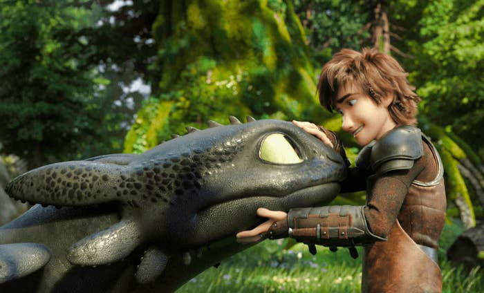Hiccup cradling Toothless's head while they both look at each other