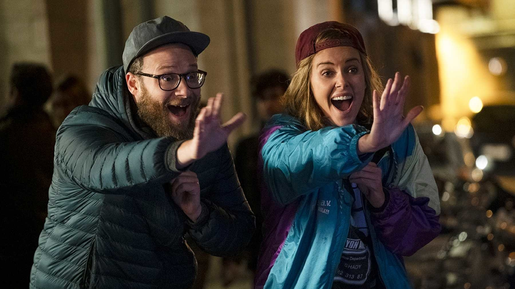 """Seth Rogen and Charlize Theron in """"Long Shot""""; they're holding up their hands in a stop motion and smiling"""