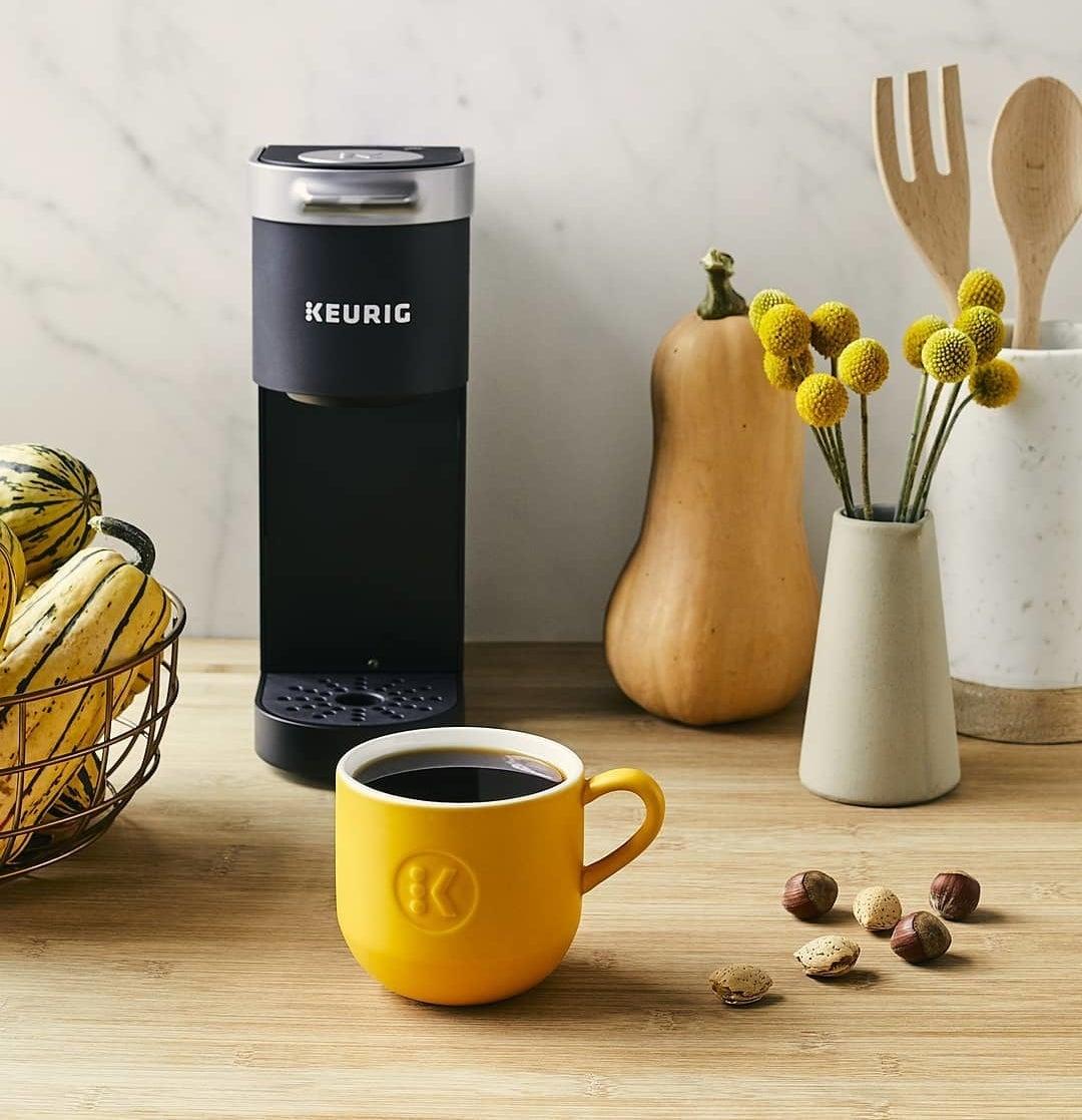 A cup of coffee beside a Keurig K-Mini