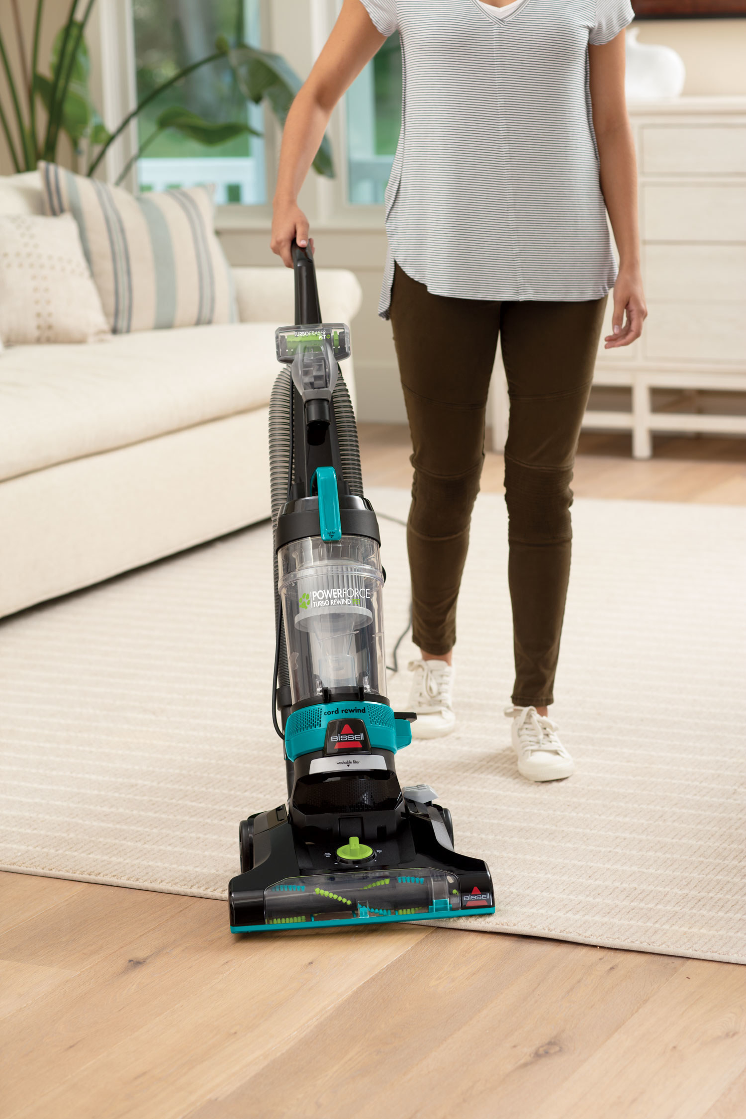 person pushing around a bissel vacuum to clean a rug
