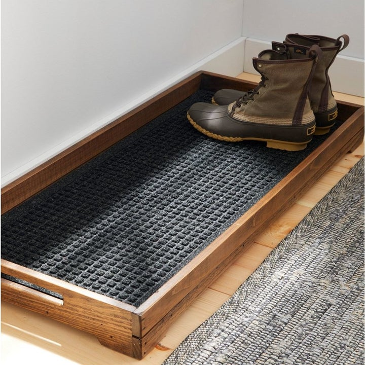a rustic wooden boot tray