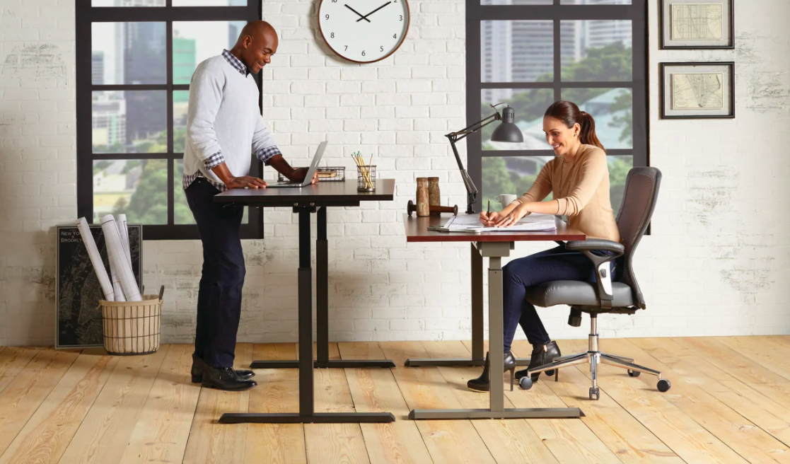 two people using two standing desks, one is sitting and one is standing