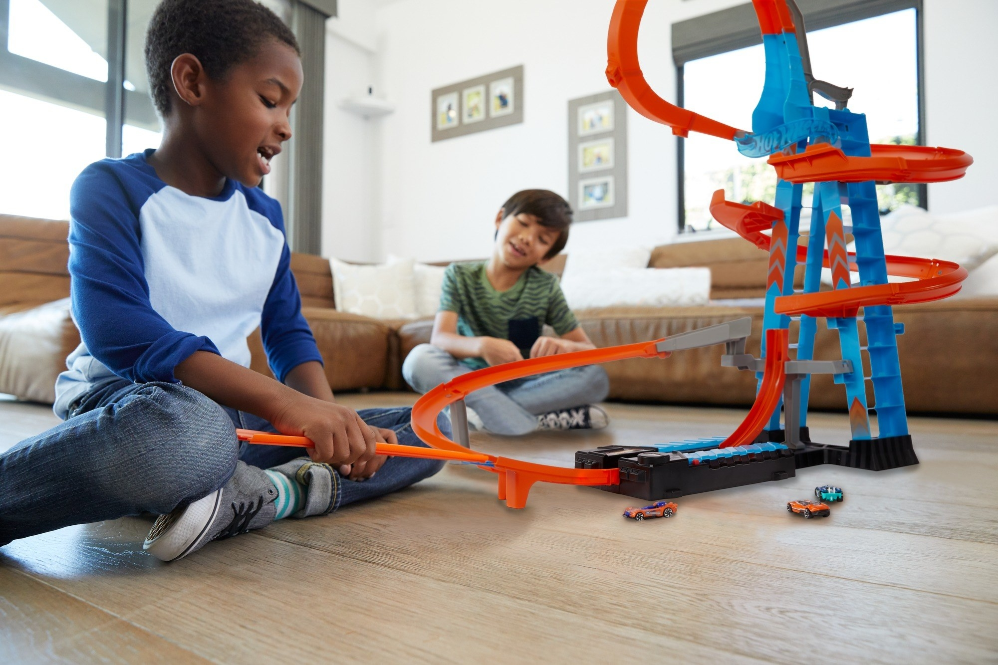 two kids play with a blue and orange hot wheels track set