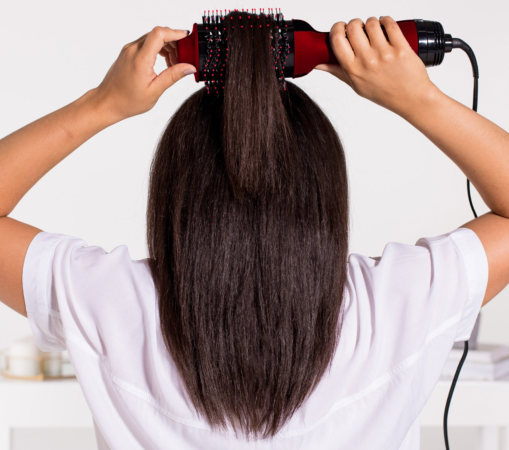 person using a revlon hot brush to style hair