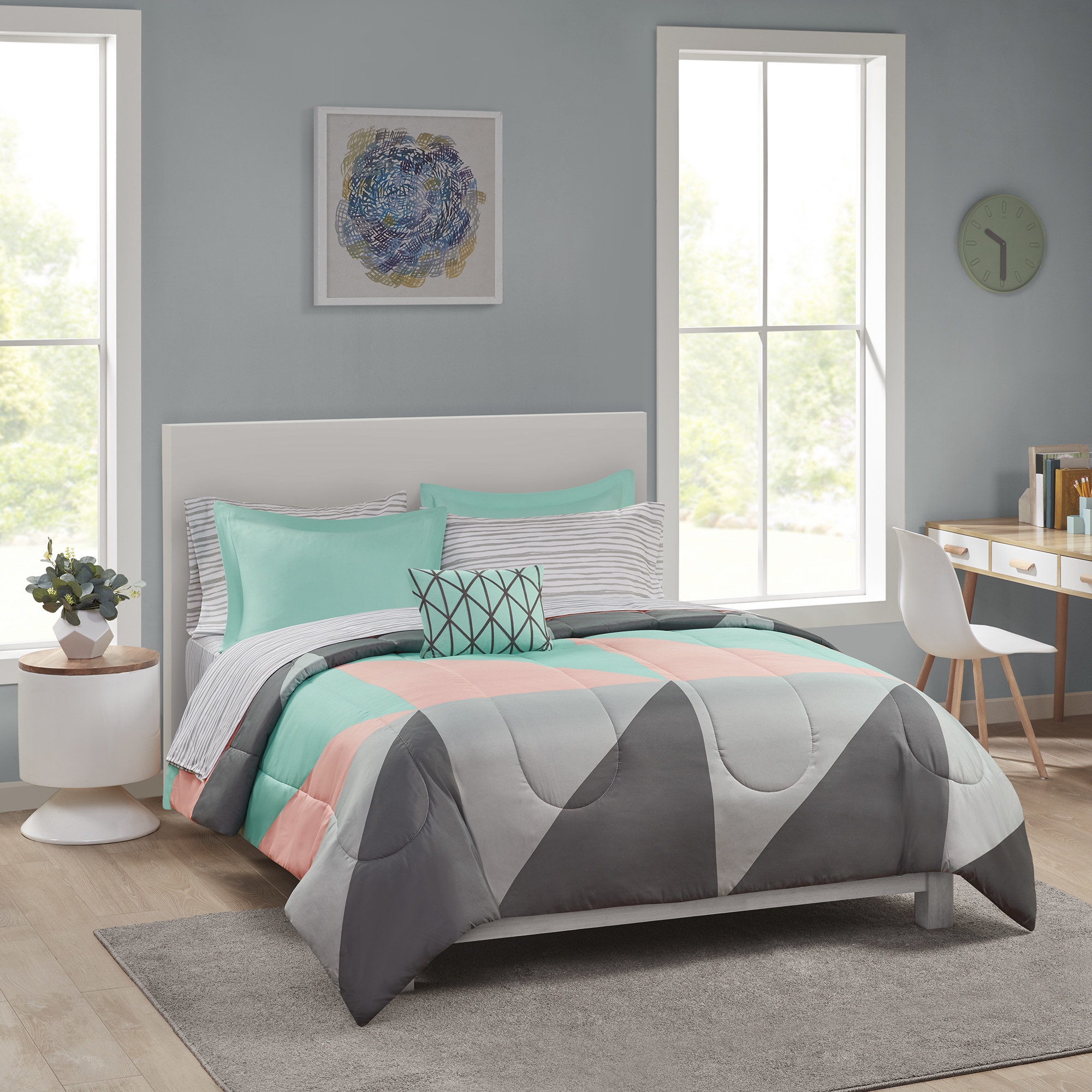 grey pink and teal comforter and bedding set on a bed in a bedroom