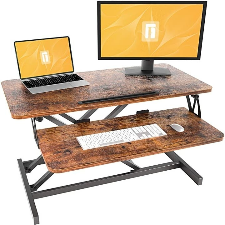 The espresso wood FEZIBO standing desk supporting a laptop, monitor and keyboard