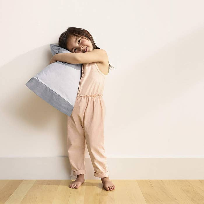 a child happily hugging the pillow