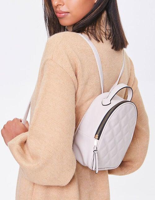 model wearing the mini backpack in cream