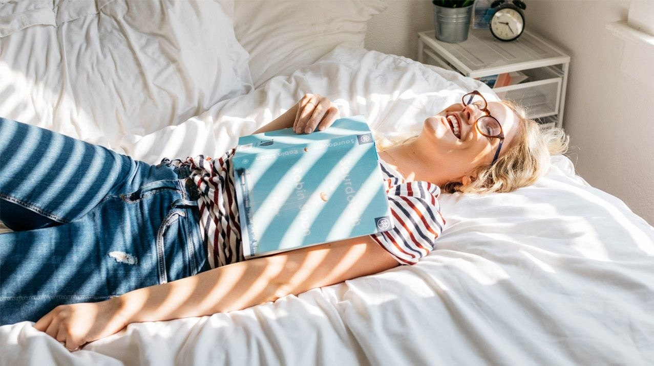 a person laying sideways on their bed with a book on their chest laughing and joyful