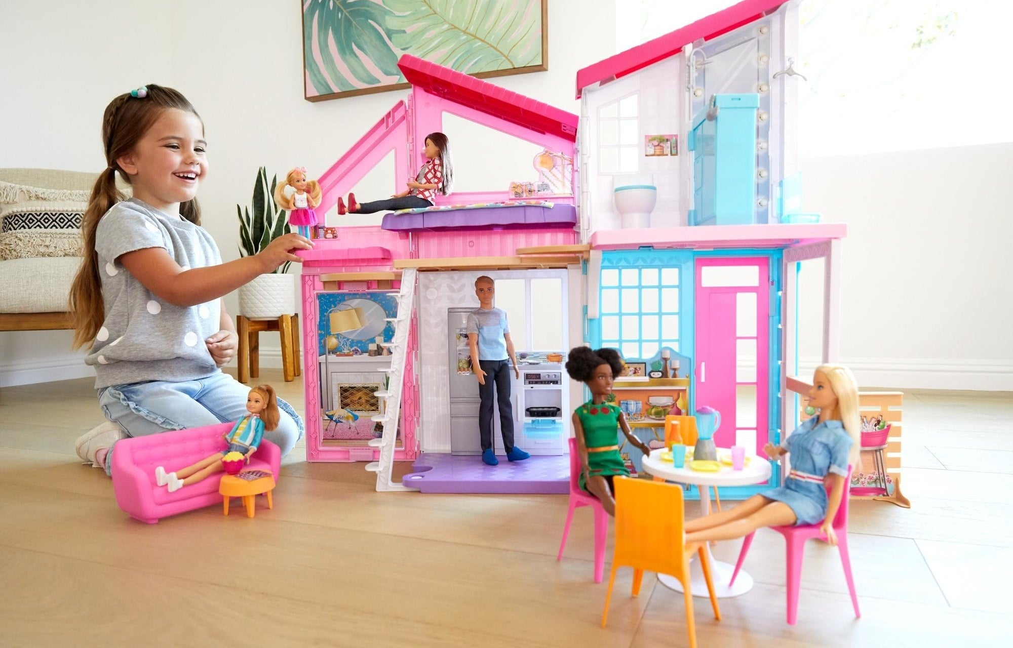 little kid playing with barbie dolls in her barbie malibu house