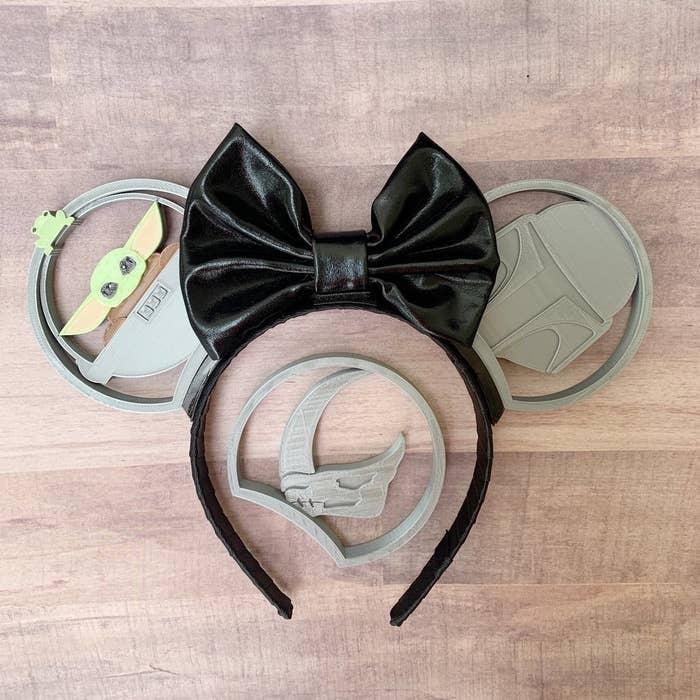 3d printed ears with a baby yoda ear, a mando ear, and a black bow