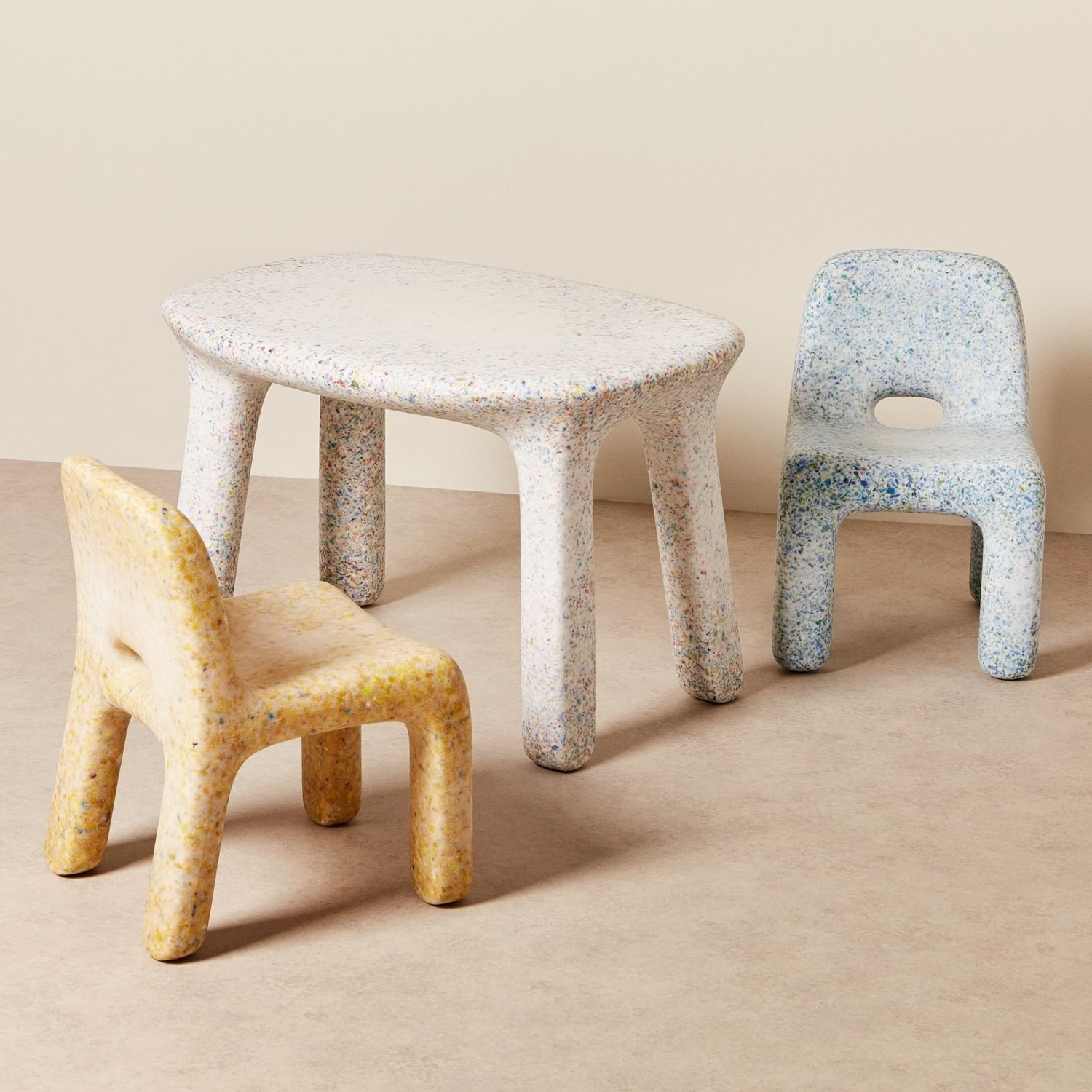 speckled desk and chairs that have a sort of rounded look as if they were left in the ocean for many years