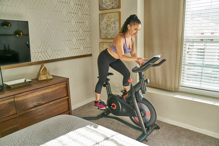 person on an at-home cycling bike in a bedroom