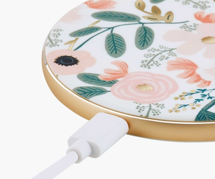Charger plugged into the white circular charger with pink floral pattern