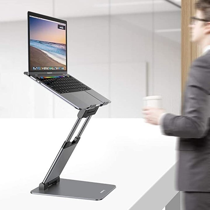 The laptop stand fully extended with a model walking past