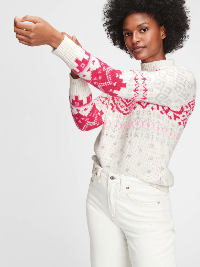model wearing a white sweater with a pink and red fair isle design