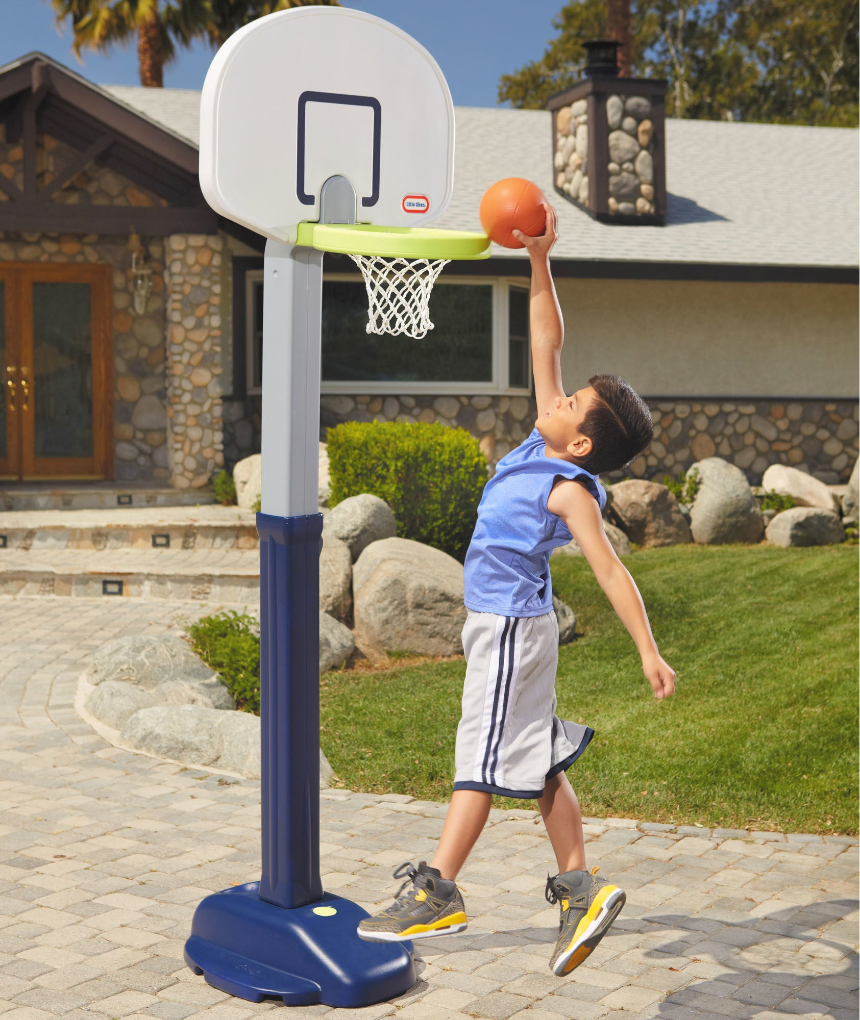 kid slam dunking a basketball into a little tikes basketball hoop