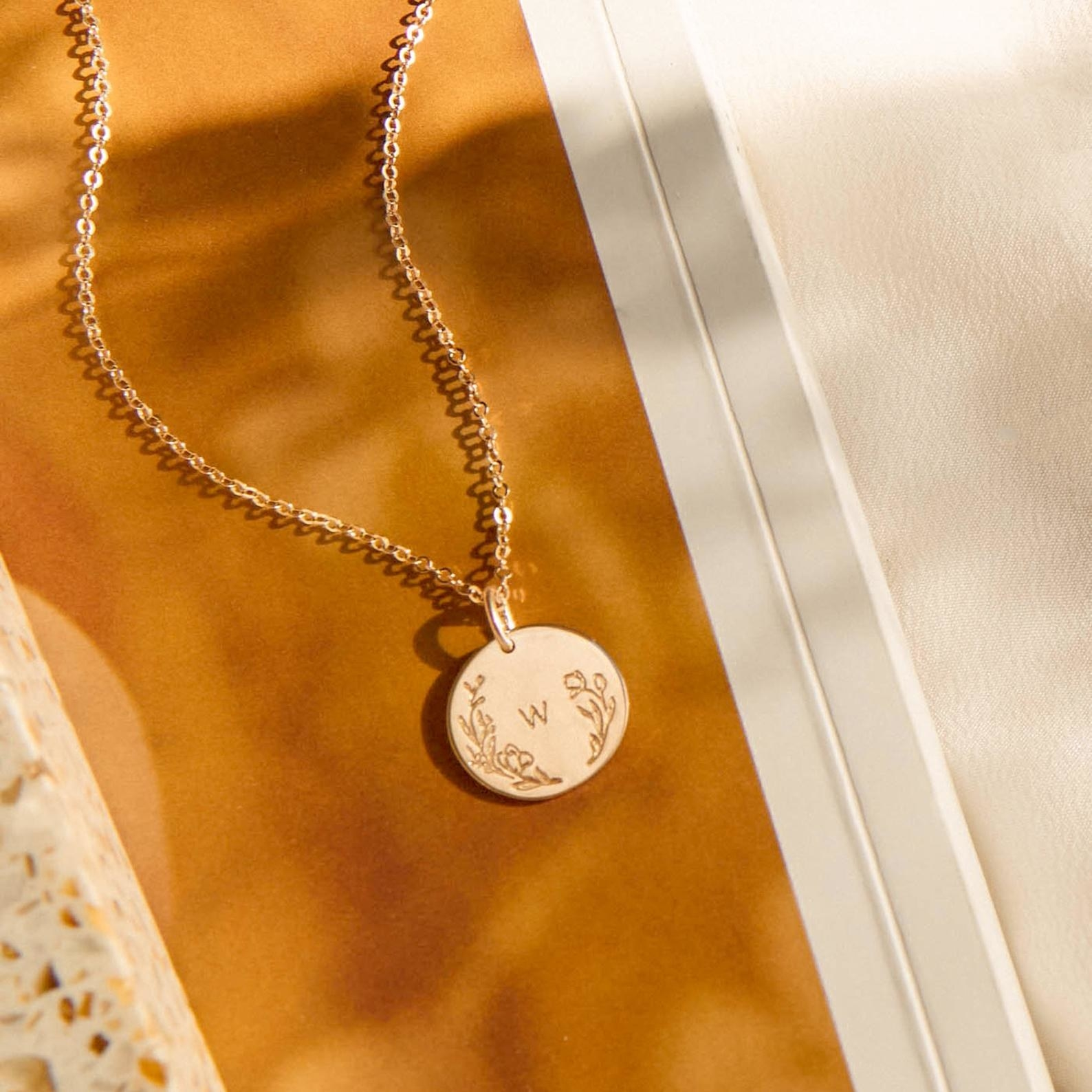 necklace with the initial w surrounded by florals