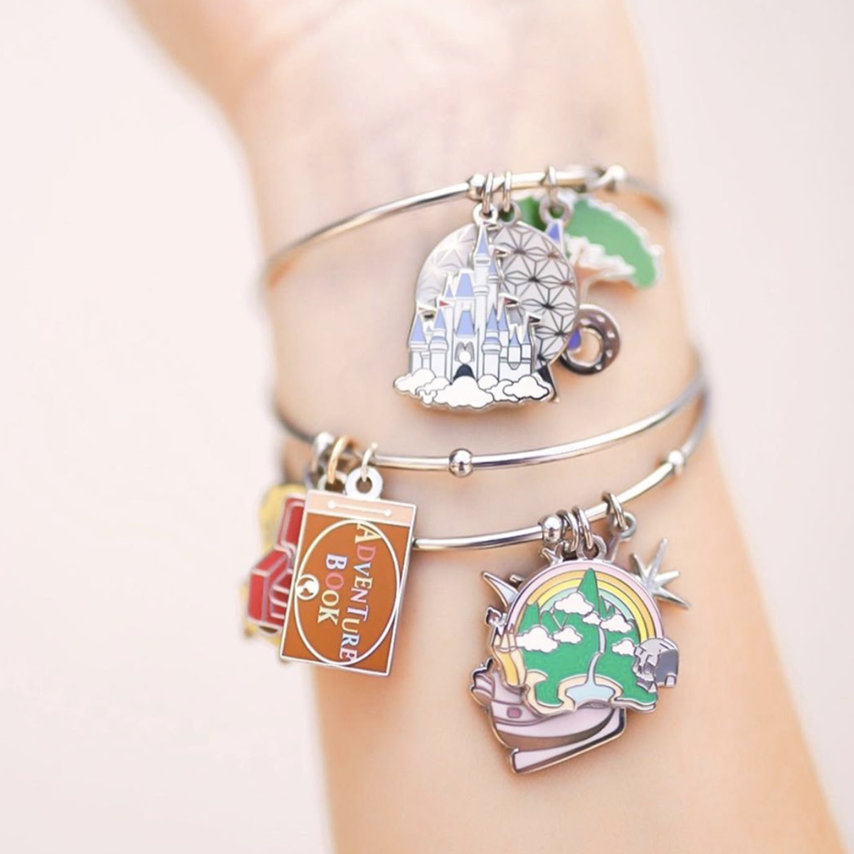 a silver bangle with different disney charms on it