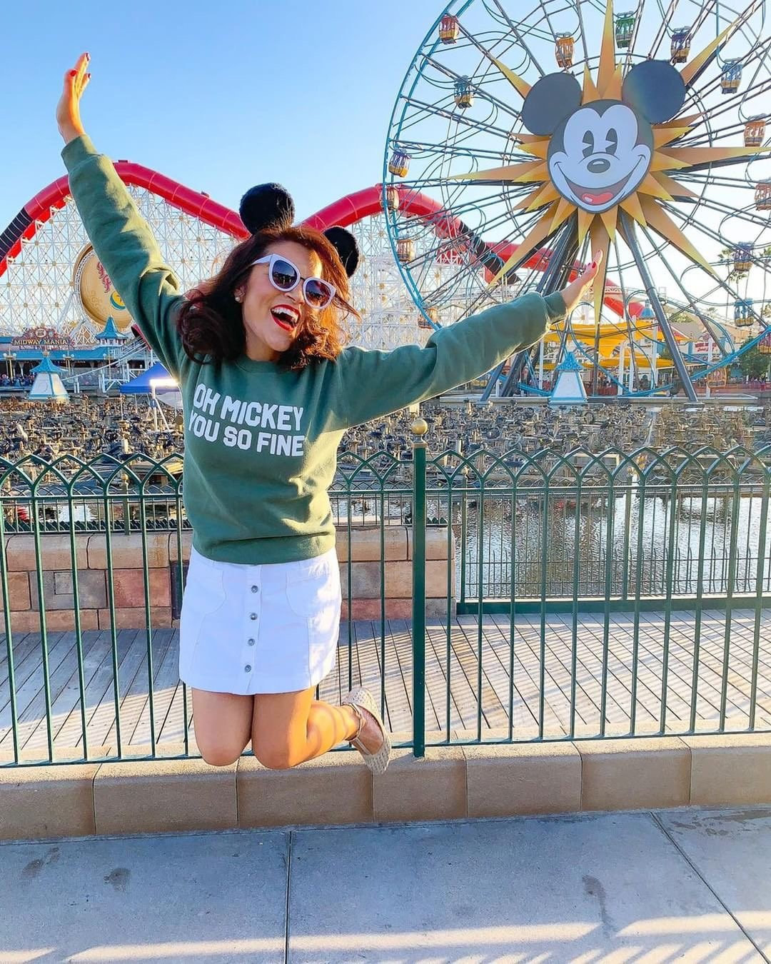 a model at disneyland jumping in their air wearing a green sweatshirt that says oh mickey you so fine on it