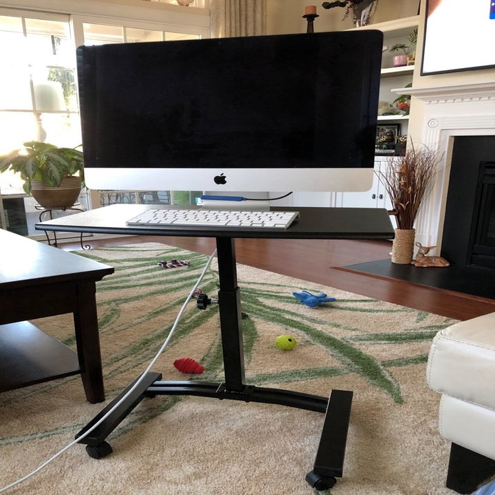 A reviewer photo of the black rolling cart supporting a monitor and keyboard