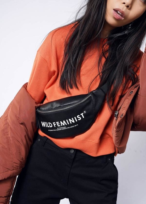 model wears black hip pack that says wild feminist