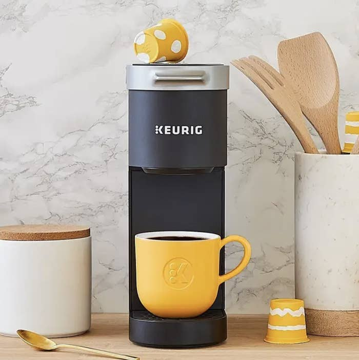 keurig on a table with a yellow mug full of coffee