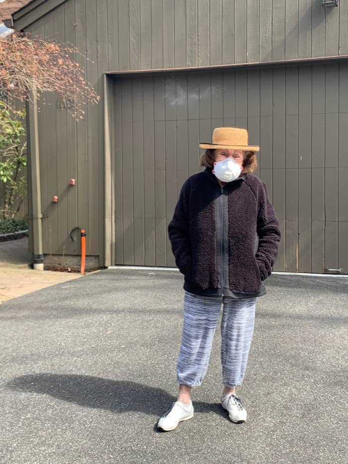 My grandma wearing a mask standing outside her house.