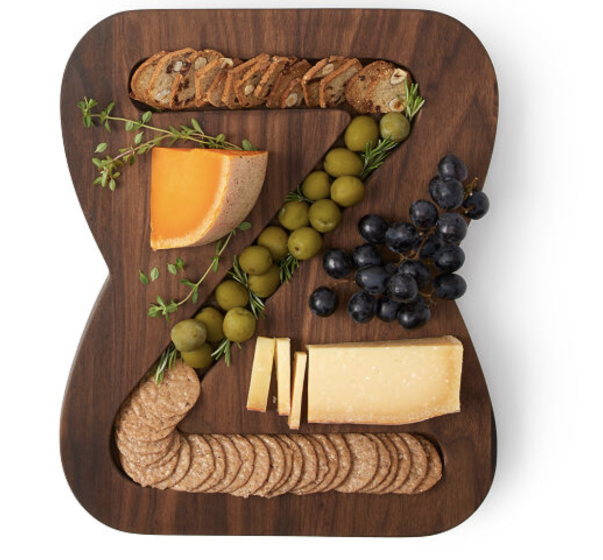 "A dark wooden cheese platter with a groove in the shape of a ""Z"" with food inside"