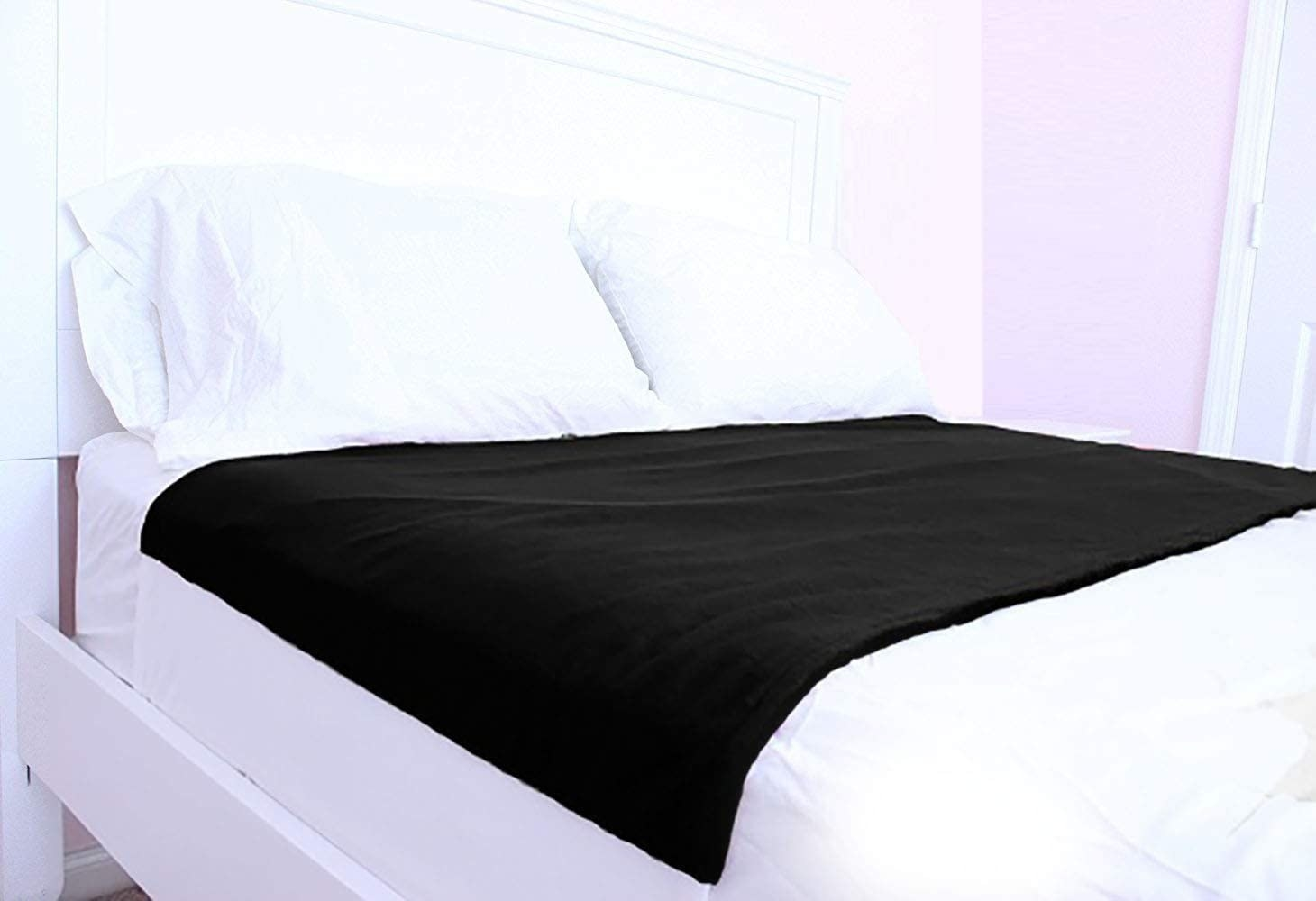 the black cycleliners period bed sheet protector on a bed