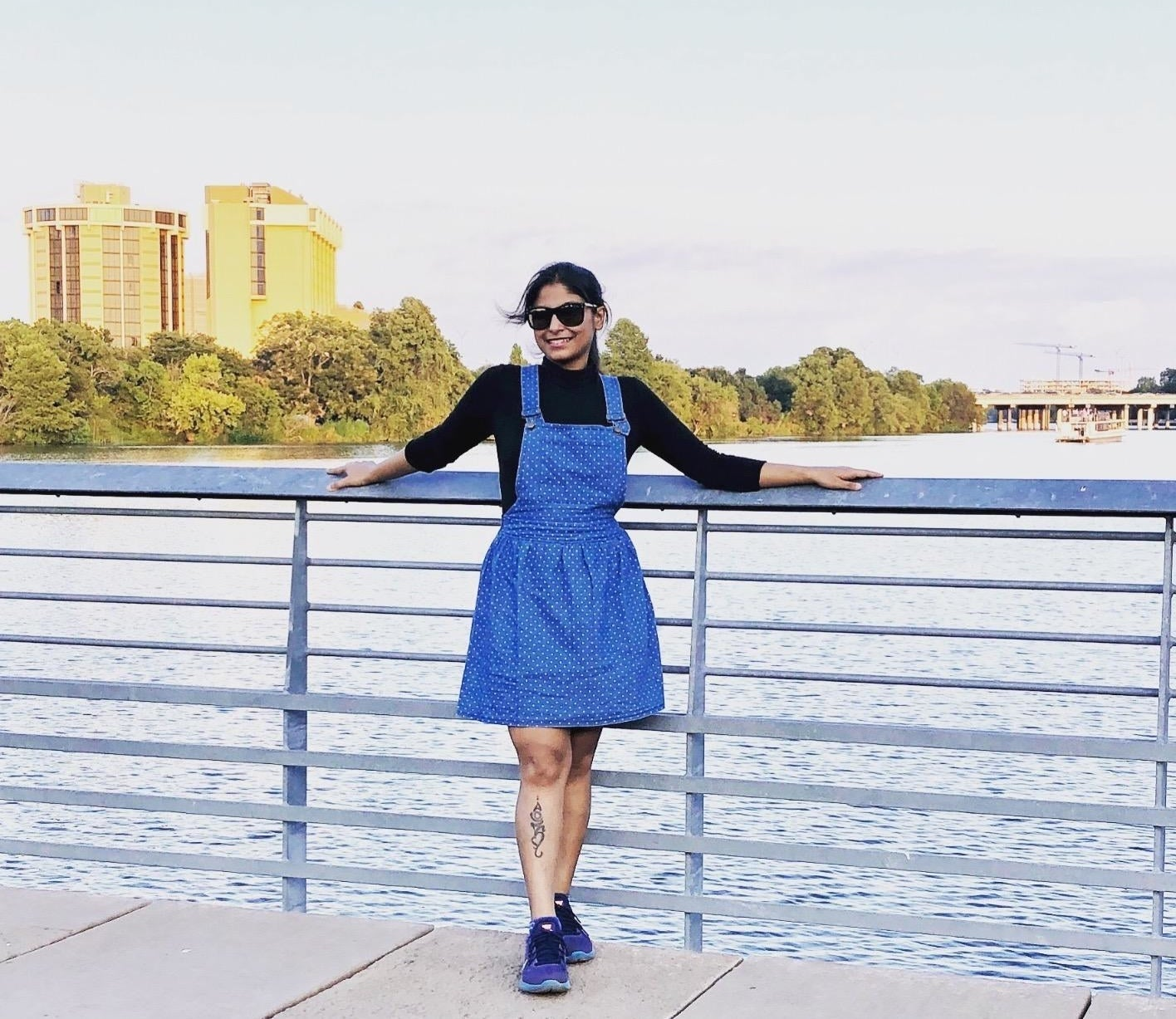 A reviewer wearing the above-the-knee, flared, polka dot, blue denim pinafore