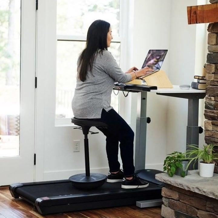 A model sitting on a stool resting on top of the treadmill portion of the products, while they operate a laptop on the desk portion