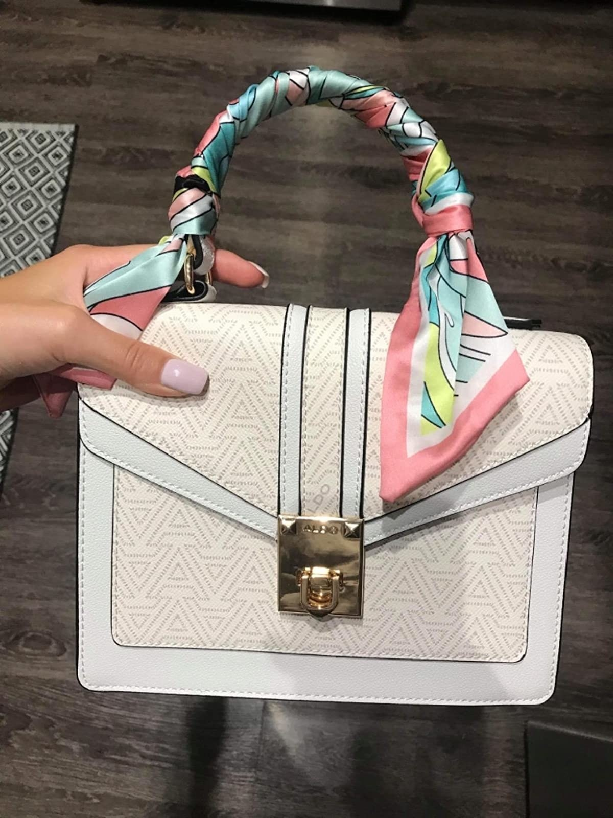 A hand holding the small square white bag with a logo print and green, coral, white, and mint print scarf around the handle