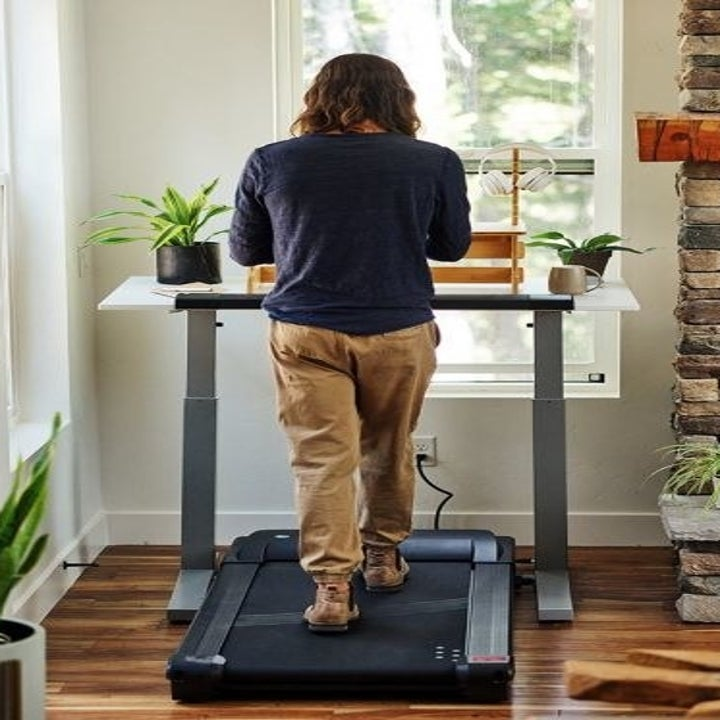The back view of a model walking on the treadmill/desk combo in a home setting