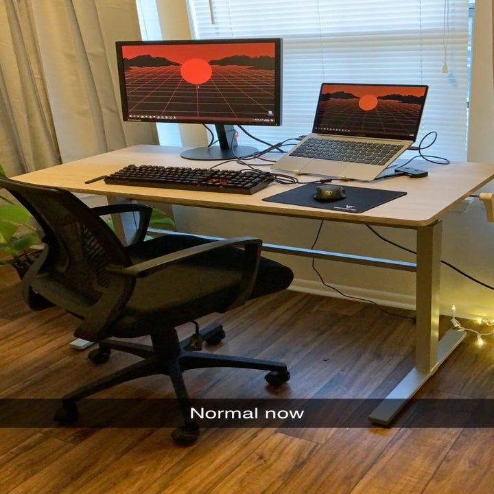 The same desk at a sitting height with an office chair in front