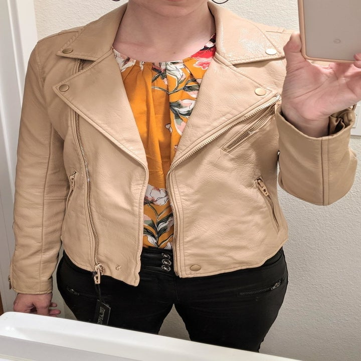 A reviewer wearing the jacket in tan