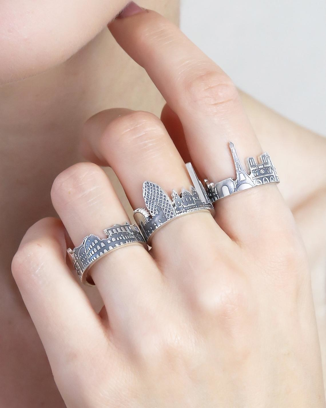 Model with three rings on hand: one with the Roman Colisseum, One of London with the Eye and Buckingham Palace, one of Paris with the Arc d'Triomphe, Eiffel Tower, And Notre Dame
