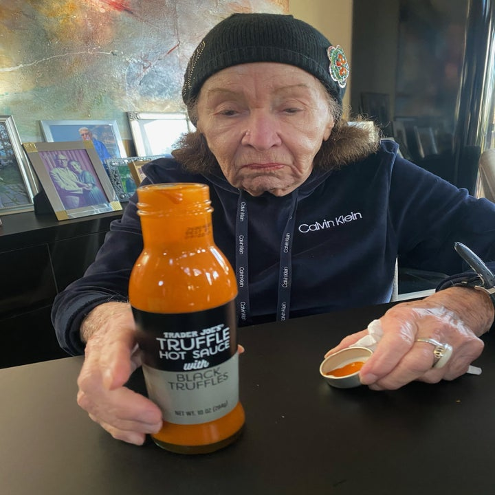 My grandma holding a bottle of Trader Joe's truffle hot sauce.