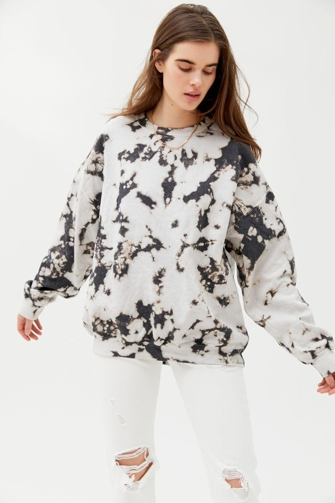 a woman wearing a black and white oversized sweatshirt