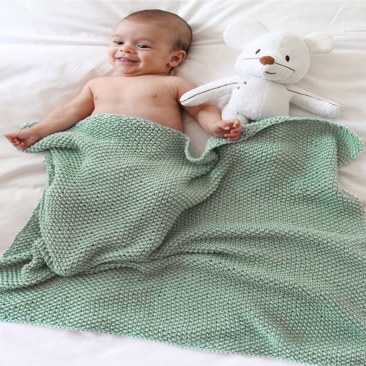a child wrapped in the dragonfly blanket