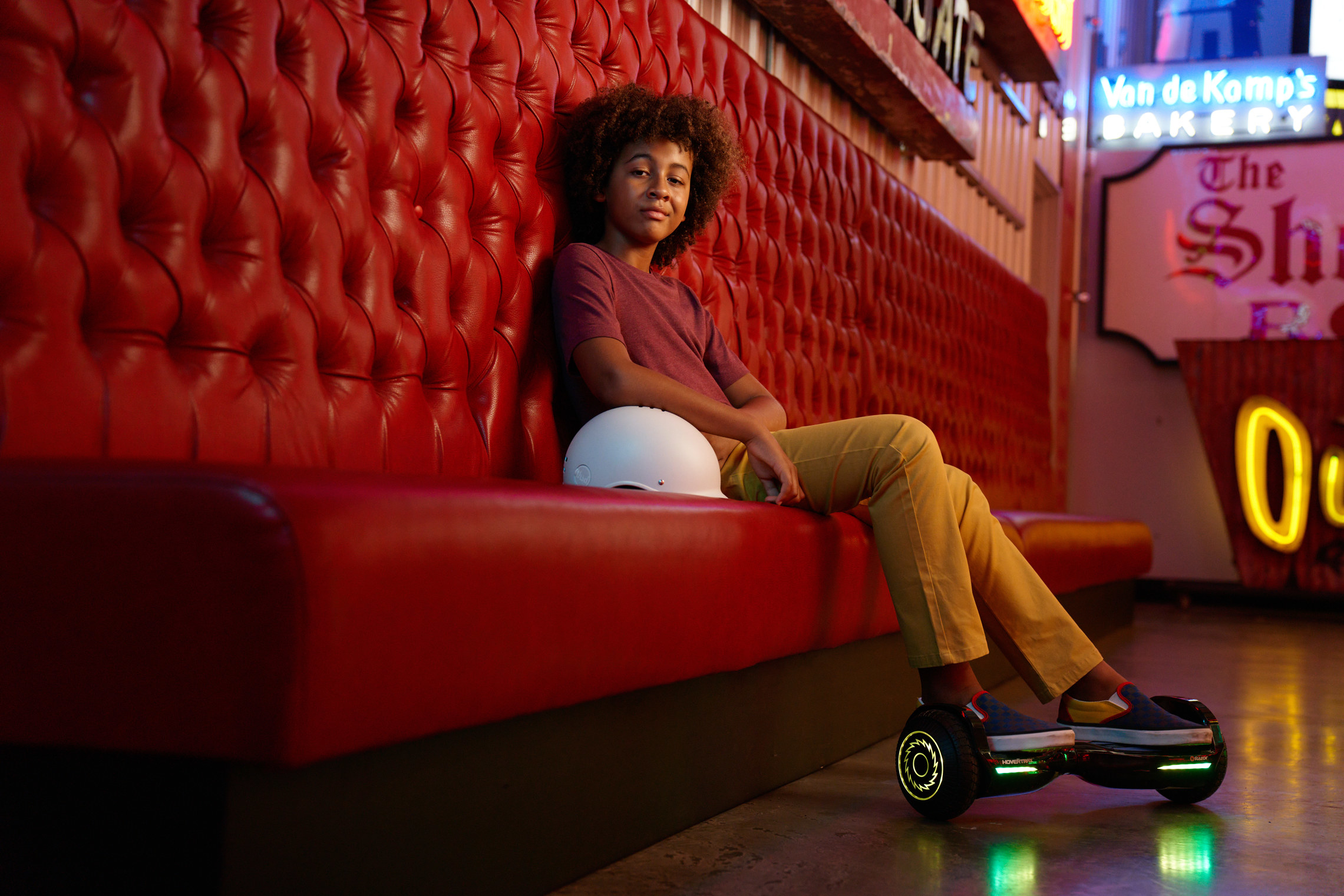 kid sitting on a couch with a lit up hoverboard on his feet