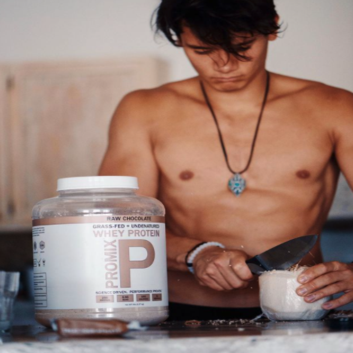 A shirtless guy cutting a coconut next to a container of Promix protein powder