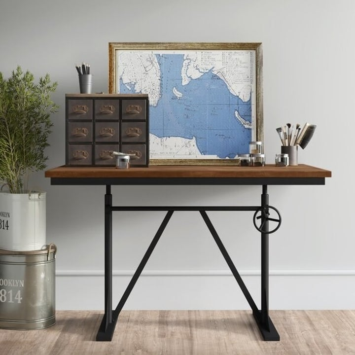 The same desk supporting a large framed map and a nine-drawer storage cube